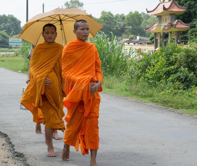 亚裔年轻修士走的早晨施舍 库存照片