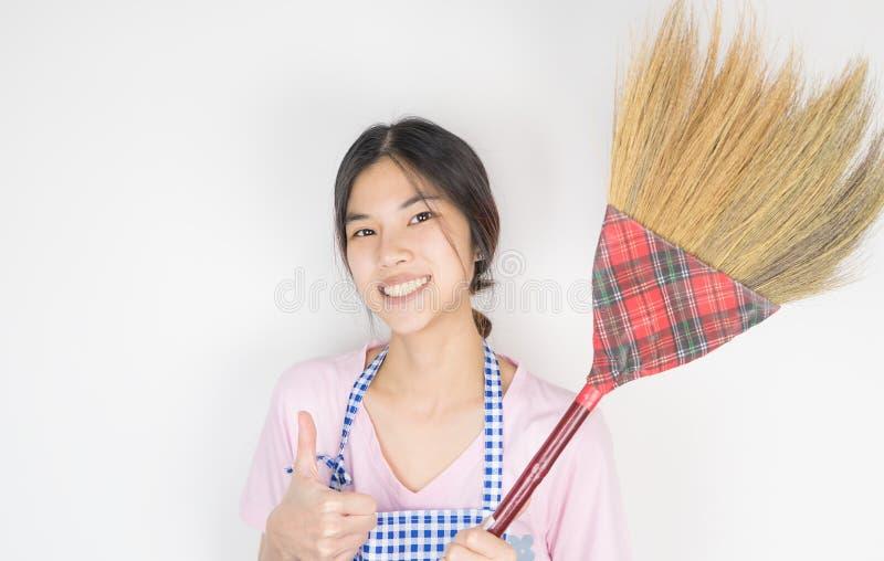 亚裔年轻主妇拿着一把笤帚被隔绝 免版税库存图片