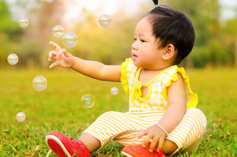 亚裔婴孩愉快在moring的时间的草与阳光 库存照片