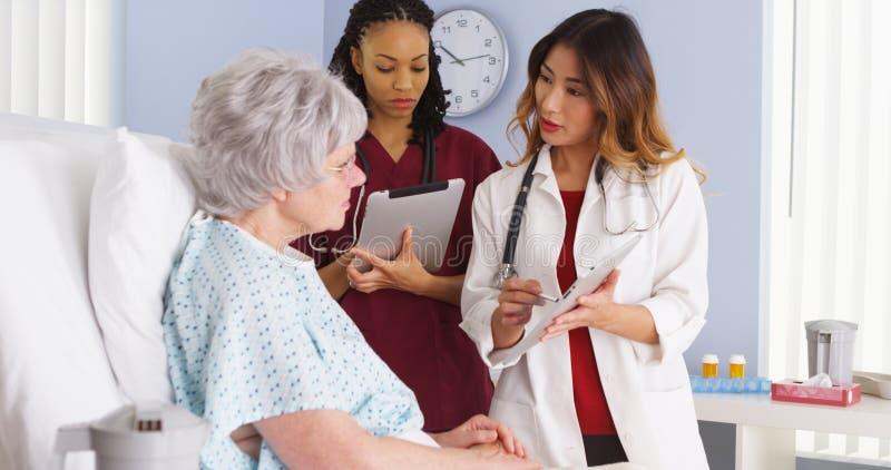 亚裔医生和非裔美国人的护士谈话与年长患者在医房 免版税库存照片