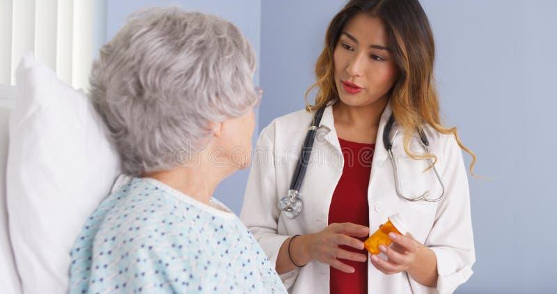亚裔医生谈话与年长妇女在床上关于处方疗程 库存图片