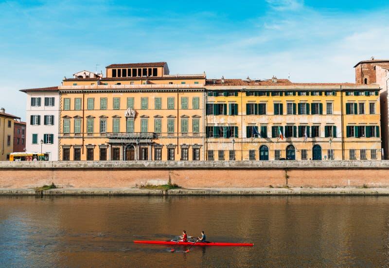 亚诺河的划船者在比萨,托斯卡纳,有惊人的五颜六色的意大利建筑学的意大利在背景中 免版税库存照片