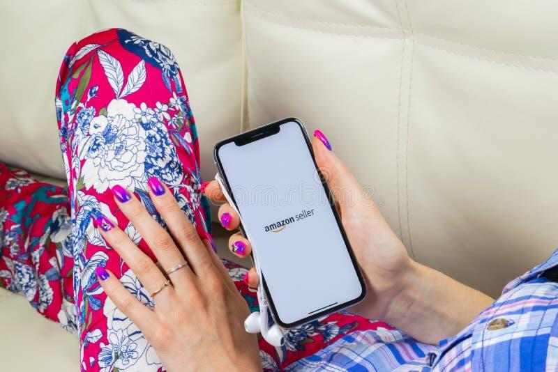 亚马逊卖主在苹果计算机iPhone x屏幕特写镜头的应用象在妇女手上 AmazonSeller app象 亚马逊卖主应用 免版税库存照片