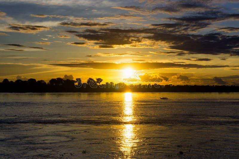 亚马逊日落和小船 免版税库存图片
