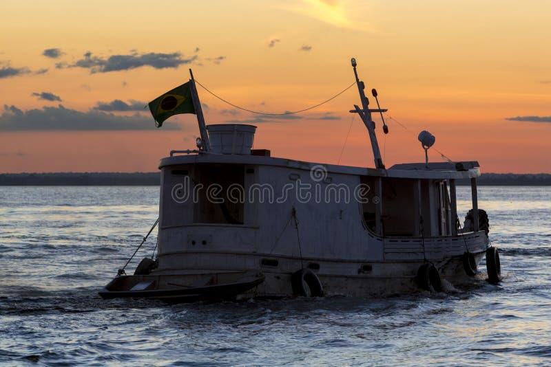 亚马逊木小船剪影在内格罗河的在马瑙斯,巴西 免版税库存图片