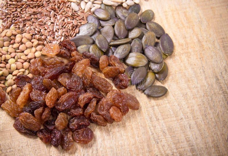 亚麻、南瓜、葡萄干、扁豆和向日葵种子在木匙子 图库摄影