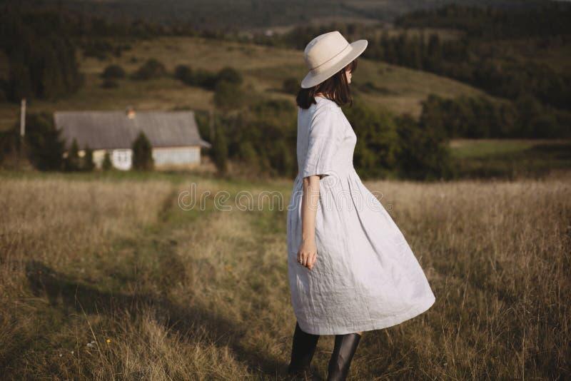 亚麻制礼服和帽子的时髦的女孩走在晴朗的领域草的在山的村庄 放松在乡下的Boho妇女, 库存照片