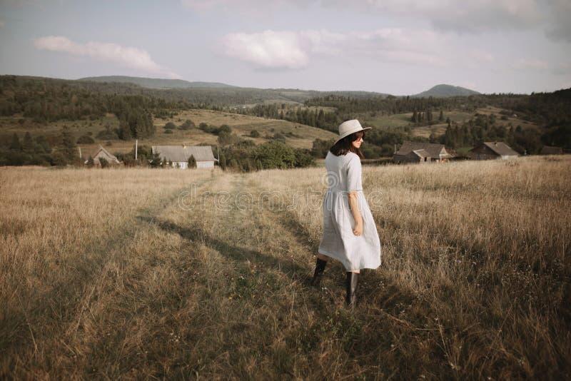 亚麻制礼服和帽子的时髦的女孩走在草本和野花中的在晴朗的领域在山 放松Boho的妇女  免版税库存照片