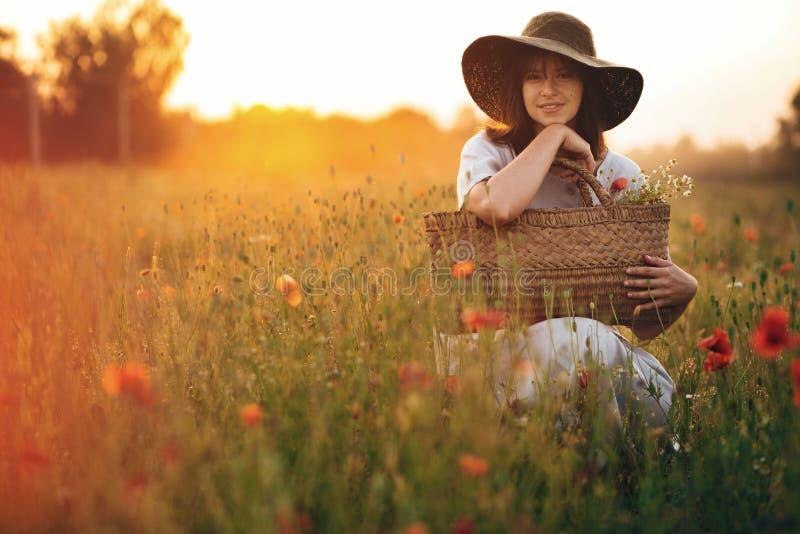 亚麻制礼服的时髦的女孩微笑在日落光的鸦片草甸的与在土气秸杆篮子的花 帽子的Boho妇女 免版税图库摄影