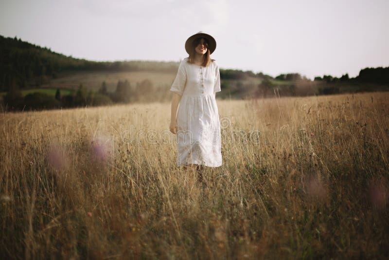 亚麻制礼服的时髦的女孩走在草本和野花中的在山的晴朗的草甸 放松在乡下的Boho妇女, 免版税库存照片