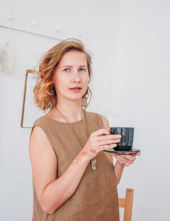 亚麻制礼服的美丽的浪漫年轻白肤金发的妇女有茶的与无刺指甲花mehendi的在手上 Eco自然美人 免版税库存照片