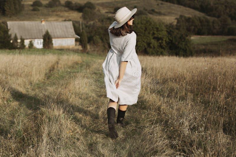 亚麻制运行和微笑在晴朗的领域草的礼服和帽子的时髦的女孩在山的村庄 放松Boho的妇女  免版税库存图片