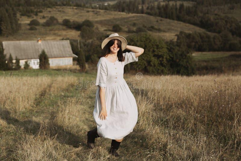 亚麻制运行和微笑在晴朗的领域草的礼服和帽子的时髦的女孩在山的村庄 放松Boho的妇女  图库摄影