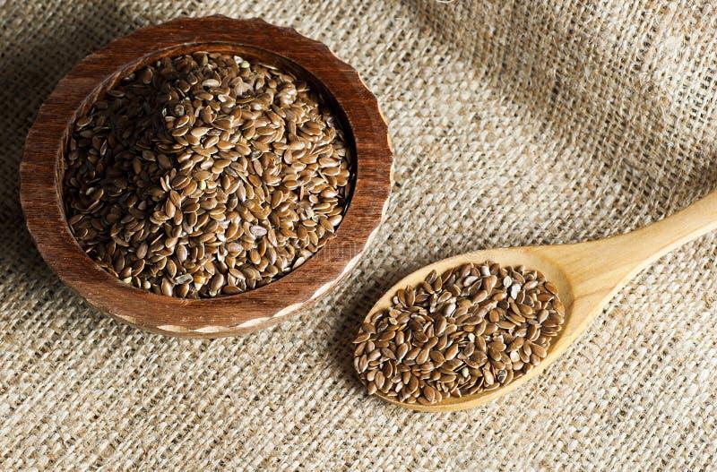 亚麻籽或油麻堆在匙子和碗在木或粗麻布大袋背景 免版税库存图片