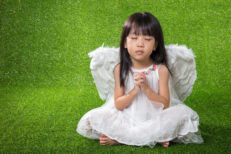 亚洲中国小女孩佩带的天使翼和祈祷 库存照片