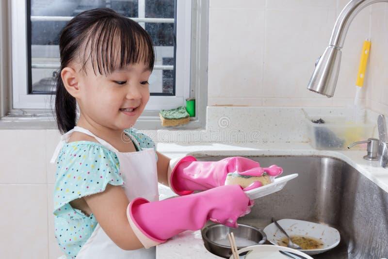 亚洲中国小女孩洗涤的盘在厨房里 库存图片