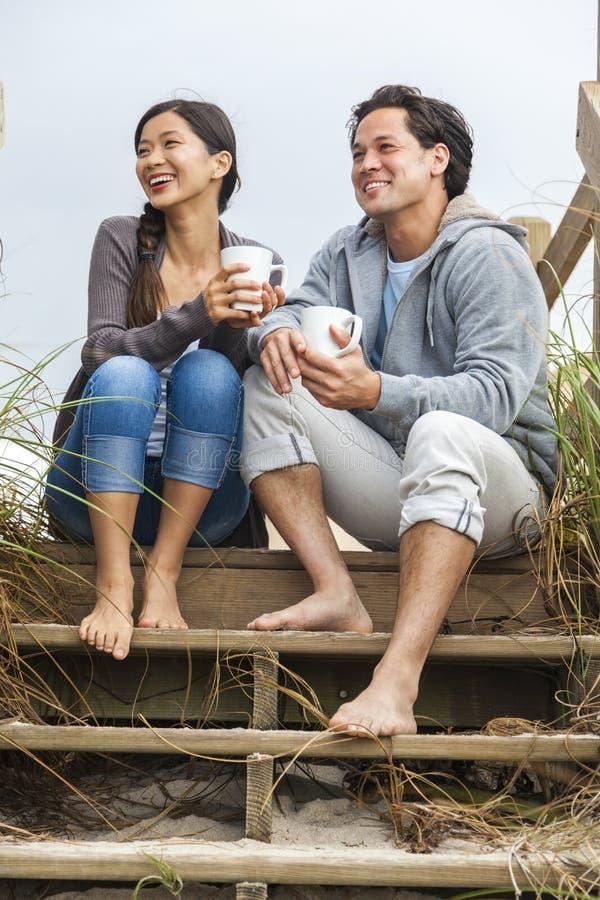 亚洲人妇女夫妇饮用的咖啡海滩步 库存照片