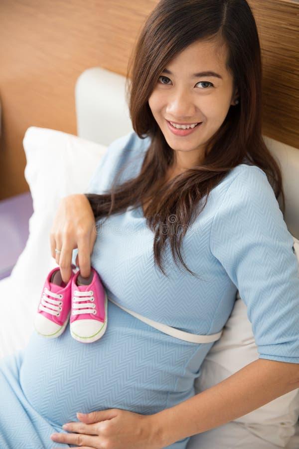 亚洲人怀孕的愉快的妇女在她的手上的拿着童鞋 库存照片