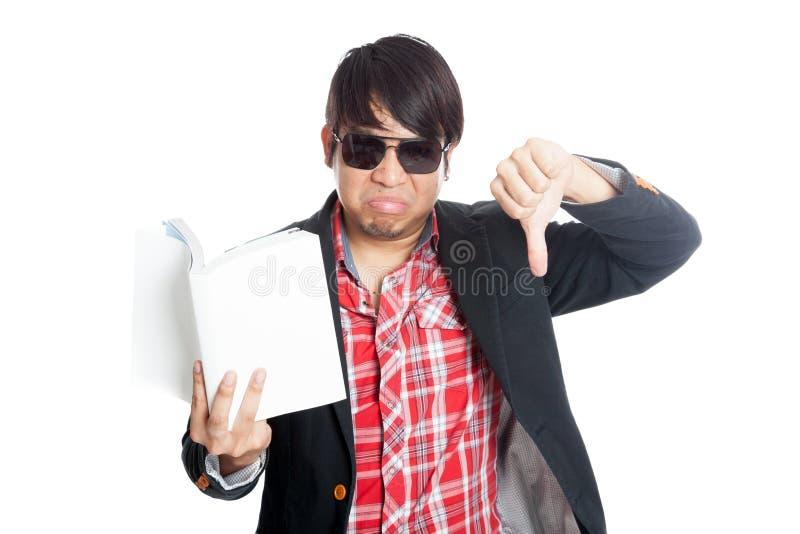 亚洲人翻倒读了书展示拇指下来 免版税库存图片
