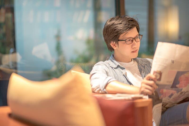 年轻亚洲偶然商人读书报纸 免版税库存照片