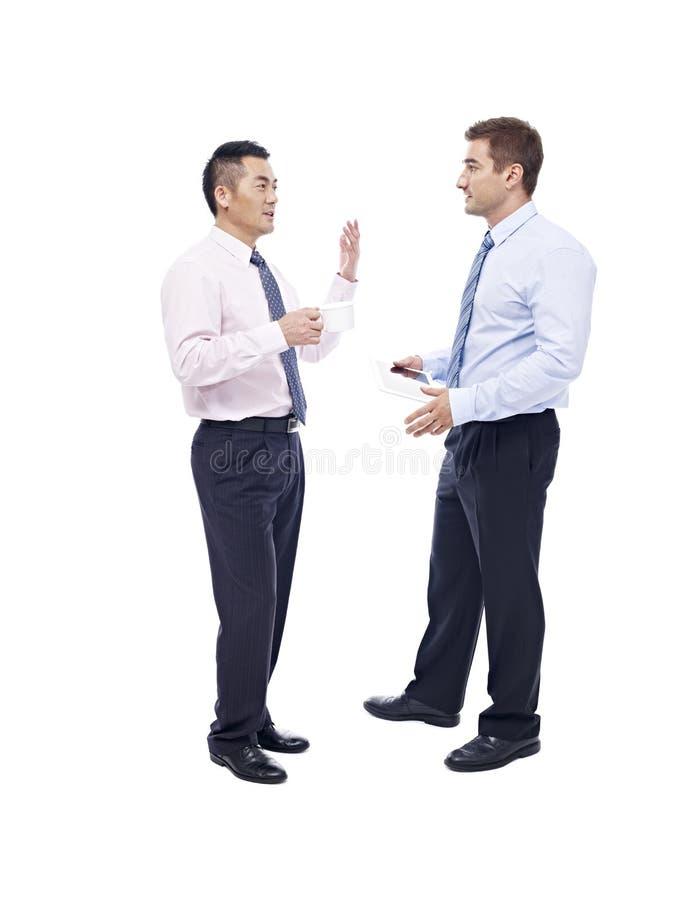亚洲和白种人商人谈话 免版税库存图片