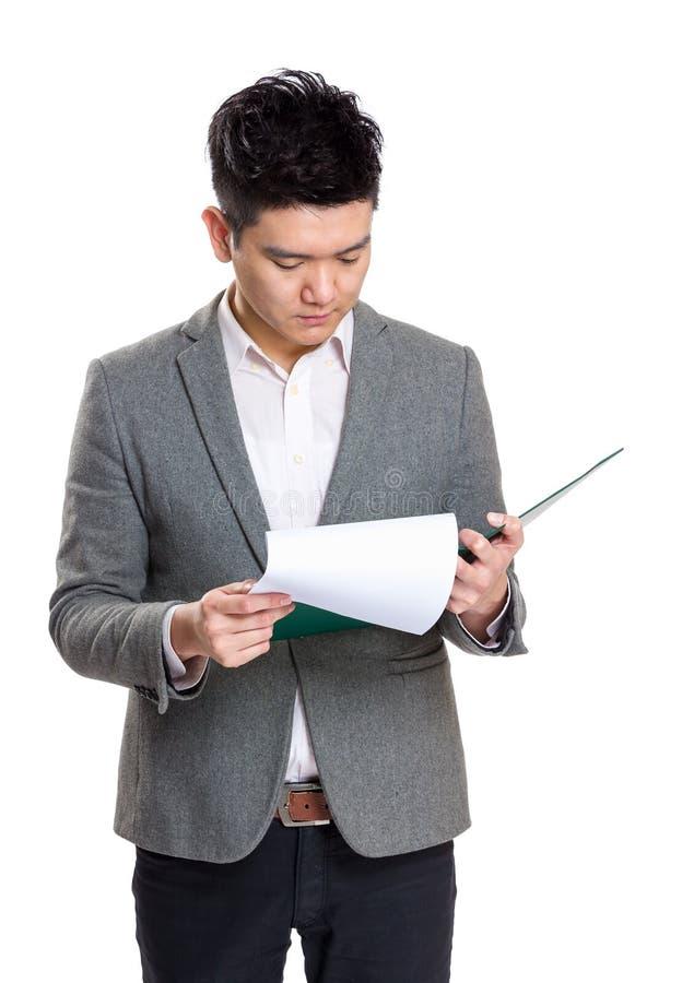 亚洲商人在剪贴板的集中读书 免版税库存图片