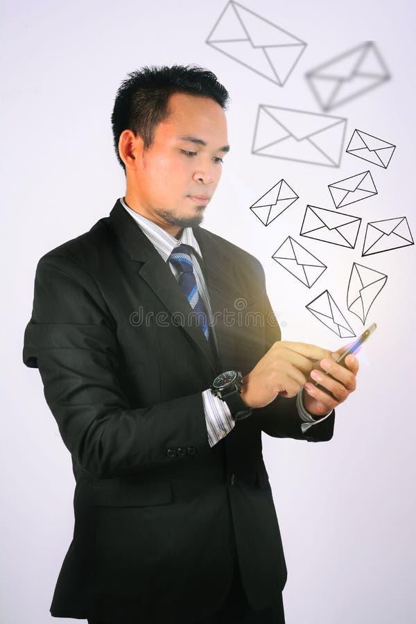年轻亚洲商人接触他的有社会网络界面商人象的智能手机 免版税库存图片