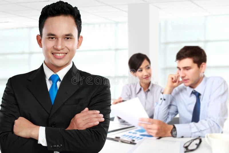 年轻亚洲商人,与后边他的队 查出在白色 免版税库存图片