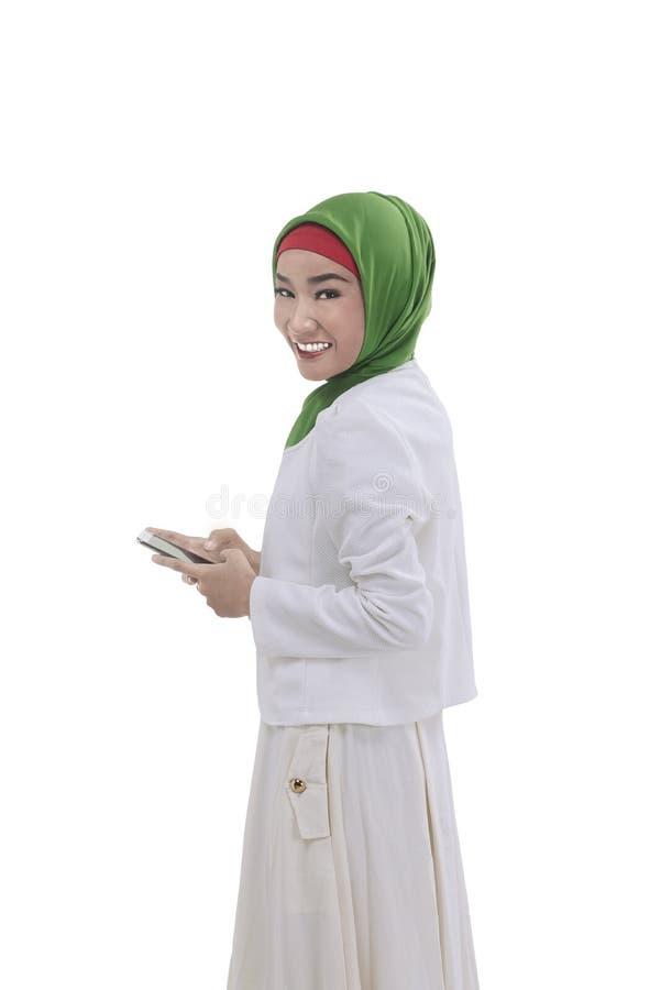 年轻亚洲回教妇女举行电话在手边 免版税库存照片