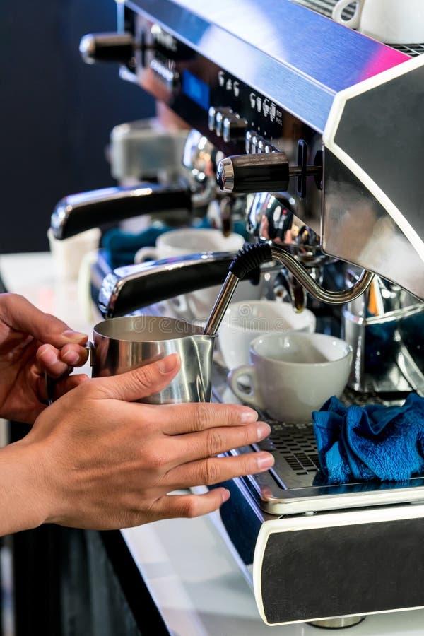 亚洲在不锈的投手的barista通入蒸汽的新鲜的牛奶有出气孔的 免版税图库摄影
