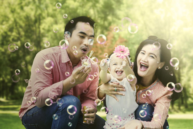 亚洲在公园的家庭吹的泡影 库存照片