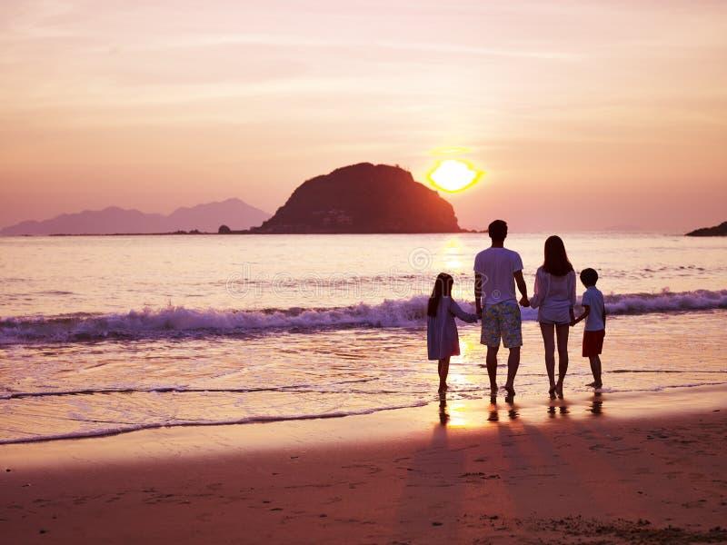 亚洲在海滩的家庭观看的日出 免版税库存图片