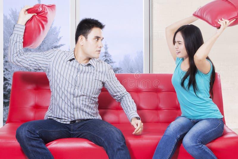亚洲夫妇争吵在红色长沙发 免版税库存图片