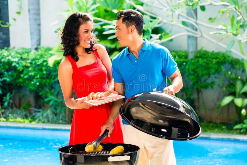 亚洲夫妇有烤肉在水池 库存照片