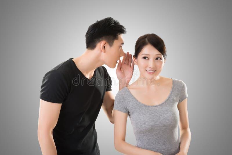 亚洲夫妇耳语 库存照片