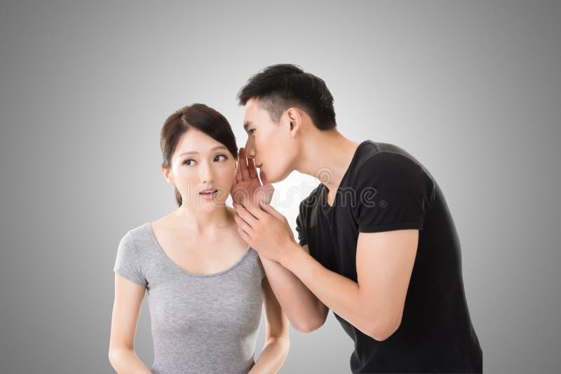 亚洲夫妇耳语 免版税库存照片