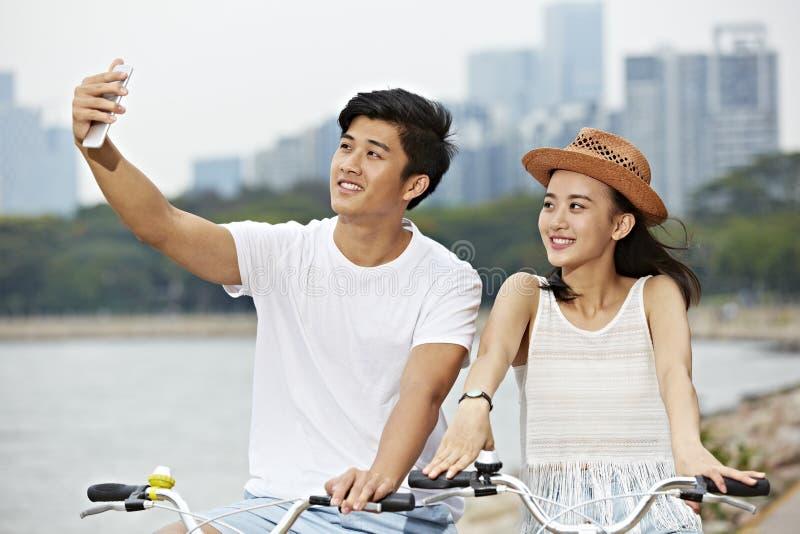 年轻亚洲夫妇骑马自行车和采取selfie 免版税库存图片