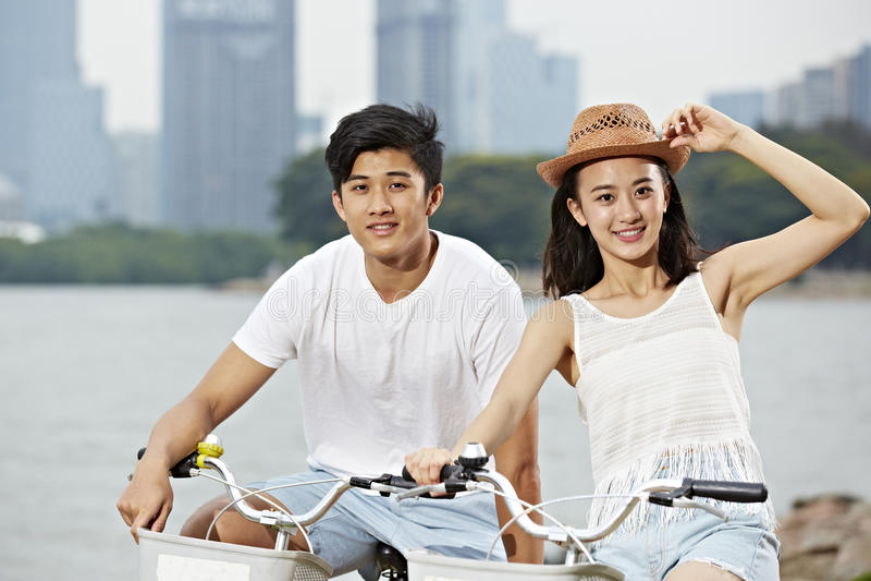 年轻亚洲夫妇骑马自行车在城市公园 库存照片
