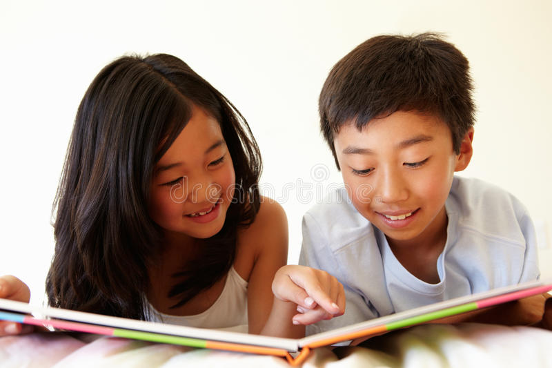 年轻亚洲女孩和男孩阅读书 免版税库存照片