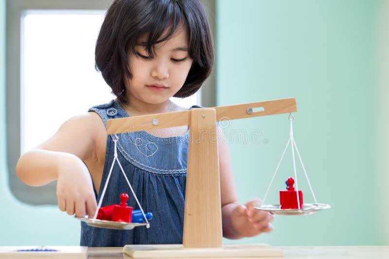 亚洲女孩平衡和认为解答的在教室 库存照片
