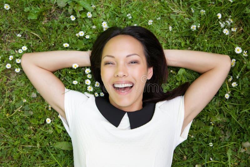 亚洲女性放松在草和微笑 免版税库存照片