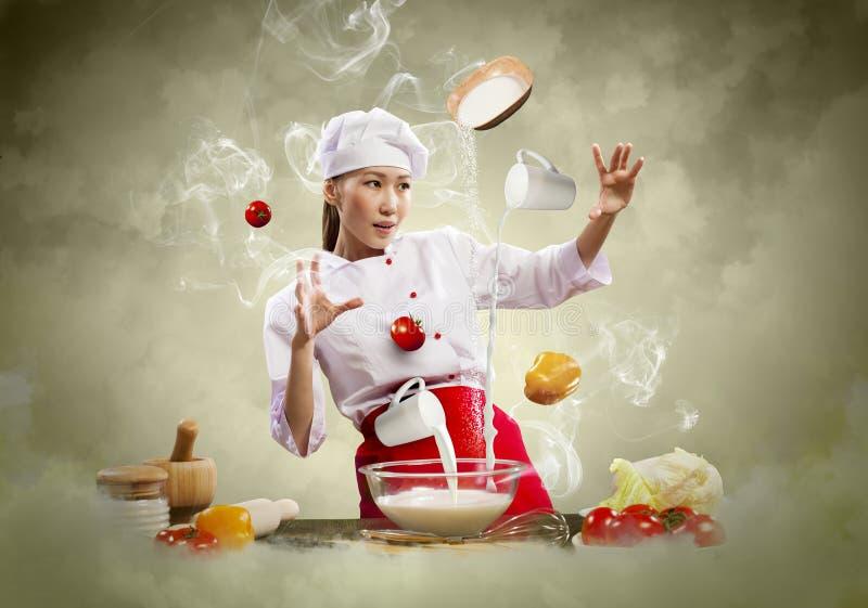 亚洲女性烹调与魔术 免版税库存图片