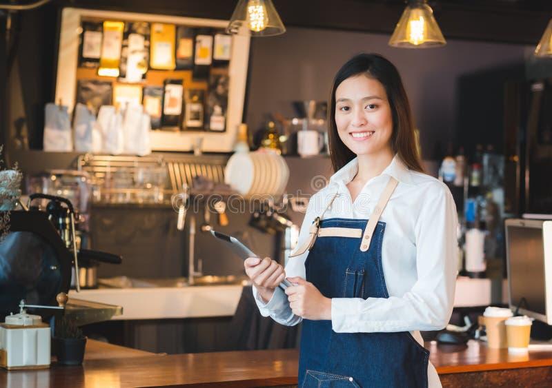 亚洲女性barista穿戴斜纹布围裙举行片剂计算机咖啡 免版税库存图片