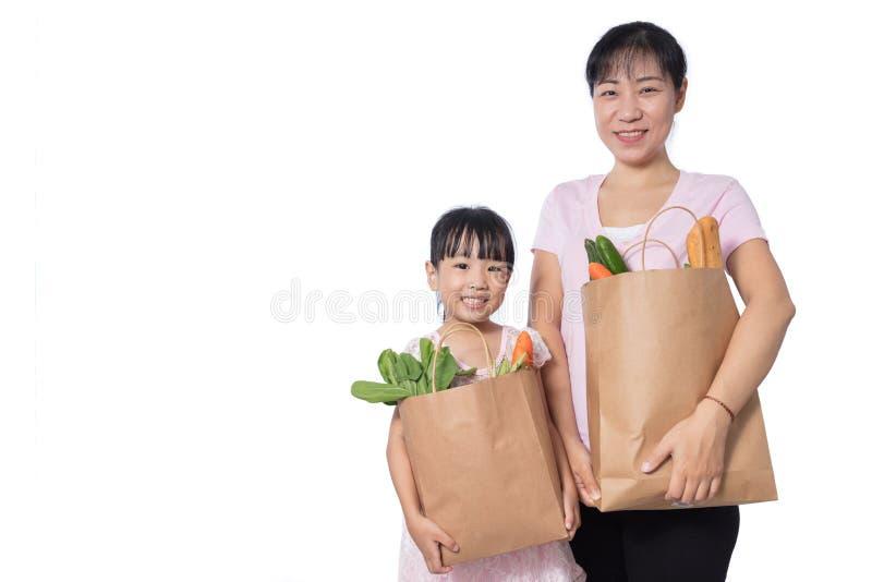 亚洲妇女和女儿运载的杂货 免版税图库摄影