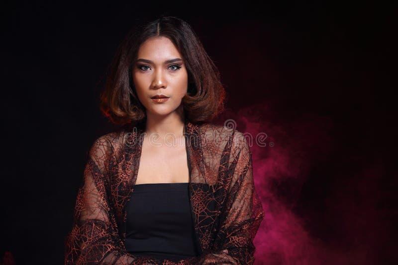 亚洲妇女时尚组成深色的头发,点燃黑色的演播室 免版税库存照片