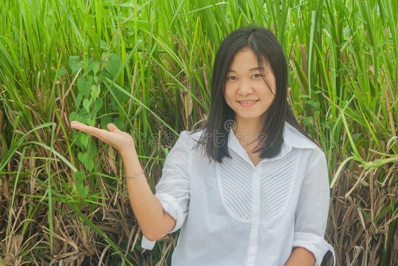 亚洲妇女画象穿戴白色衬衣,举行开放手和微笑 免版税图库摄影