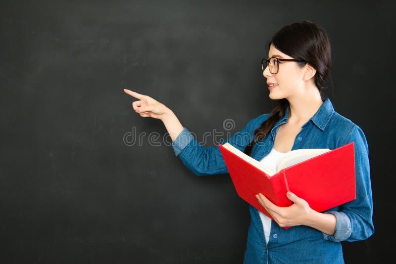 亚洲学生介绍她的站立在blackboa前面的工作 免版税库存照片