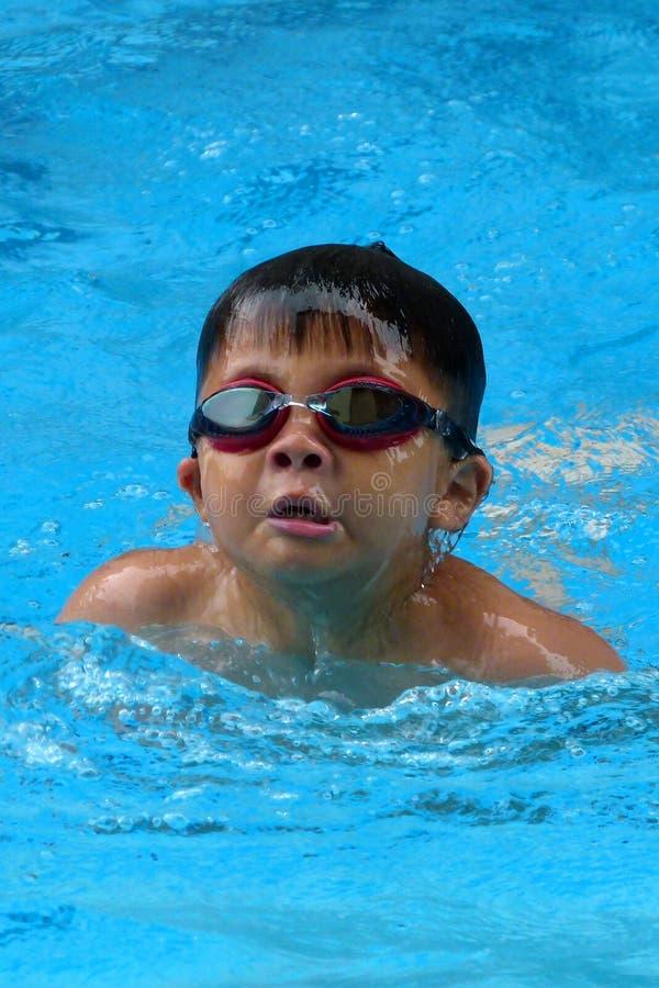 亚洲孩子在游泳池游泳-蝴蝶样式采取深呼吸 库存图片