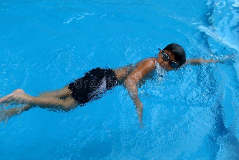 亚洲孩子在游泳池-爬泳样式作为呼吸游泳 免版税库存图片