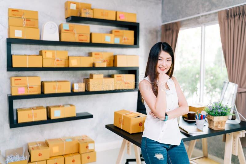 年轻亚洲小企业主在家办公室,网上营销包装和交付场面 免版税图库摄影